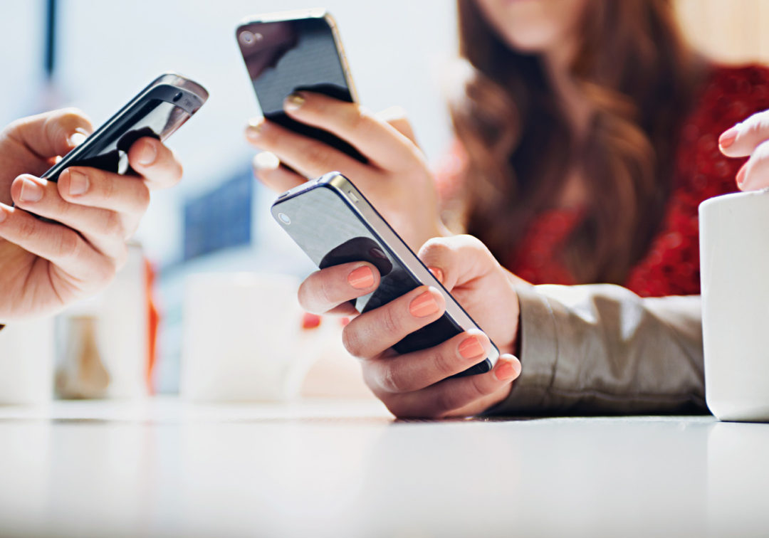 Mãos escrevendo em seus celulares