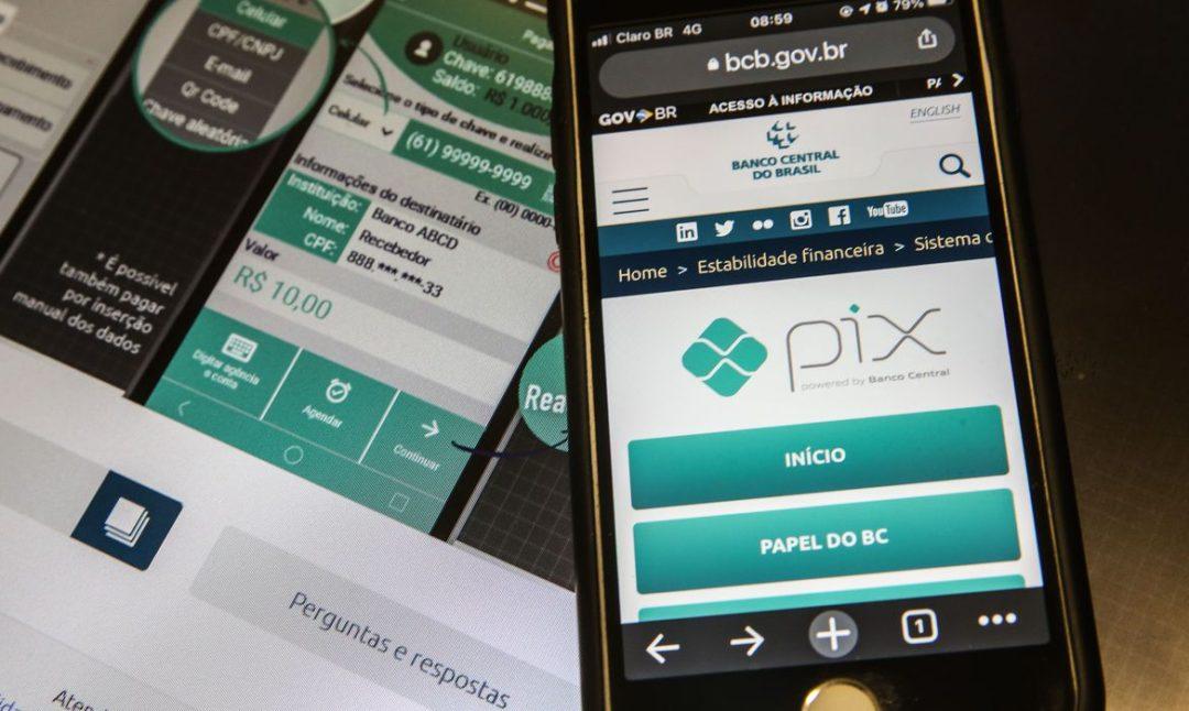 Aparelho celular com o Pix aberto em um fundo com um site de transações financeiras